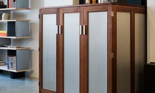 Custom cabinet to house a wine cooler and home bar with perforated aluminum door and side panels
