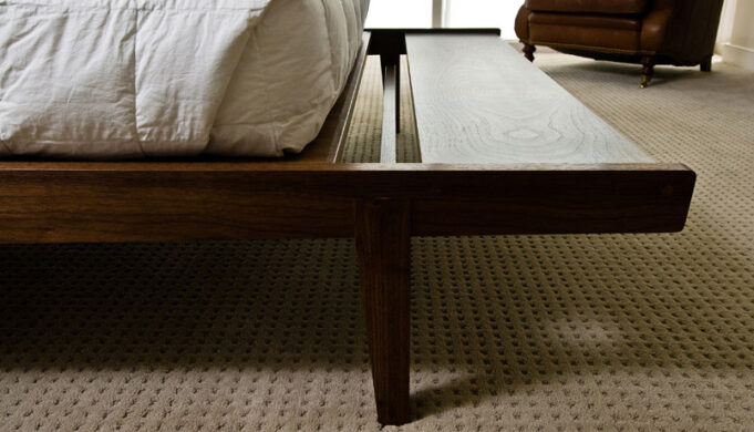 Cantilevered bench extension closeup of Tapered Bed by Infusion Furniture - black walnut