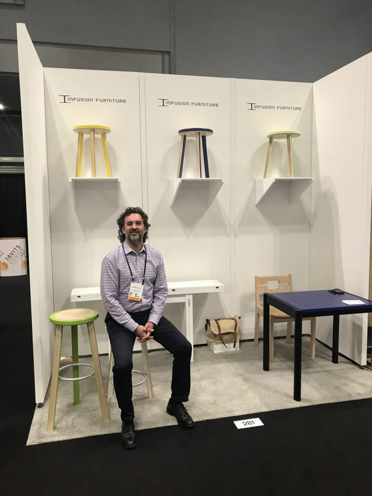 Quentin Kelley at the Infusion Furniture booth showing the Trio Stools and Transformer Table - ICFF 2017